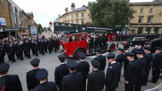 Firefighters lining the streets as a fire engine carries Stephen Hunt's coffin