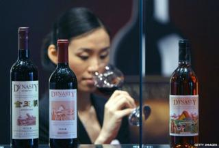 A shelf of Chinese wine, with woman tasting in background