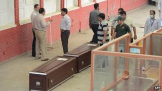 Pakistani and Slovakian officials stand next to the coffins of Slovakian climbers as they make arrangement to move them from the hospital in Islamabad on 27 June, 2013