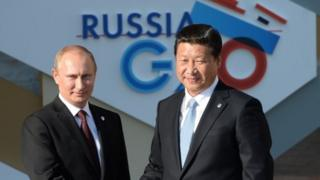 Russian President Vladimir Putin (L) greets his Chinese counterpart Xi Jinping during the official welcome of heads of delegations of G20 member states