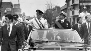 Gen Augusto Pinochet (left) waves from the motorcade in Santiago, shortly after his coup that killed President Allende on 11 September 1973.