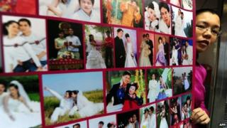 Gong Haiyan poses beside a poster in her Beijing office of photographs of married couples who met on her website (file photo)