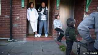 Family outside council home in Salford