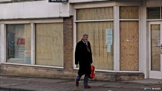 A man walks past some boarded up shops