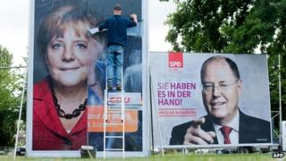 A man puts on election billboards featuring Angela Merkel and her challenger Peer Steinbrueck. Photo: 9 September 2013