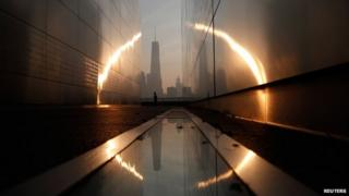 A man runs past the 9/11 Empty Sky memorial at sunrise across from New York's Lower Manhattan and One World Trade Center in Liberty State Park in Jersey City, New Jersey, on 11 September 2013