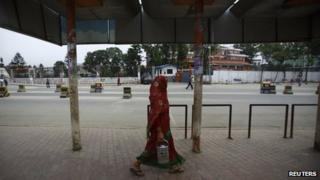 A woman walks past an empty bus stand during a general strike in Kathmandu September 12, 2013