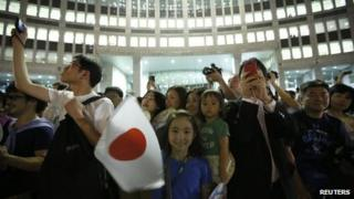 """Girl waves Japan's national flag as visitors take photos during an event titled """"Tokyo 2020 Host City Welcoming Ceremony"""