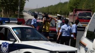 Chinese police detain a journalist at a checkpoint on the road to the riot-affected Uighur town of Lukqun, Xinjiang province, on 28 June 2013