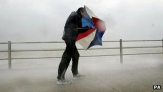 Walker battling wind and sea waves on a promenade seafront