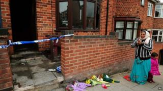 A woman prays outside the Leicester house