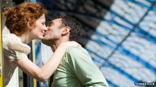 Couple kissing at a train station