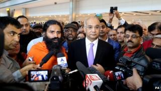 Swami Ramdevji and Keith Vaz in a crowd, facing reporters holding out microphones and cameras