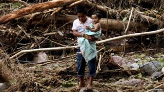 A boy holds a child in his arms while crossing a river on the mountain range of Zihuatanejo in Guerrero state on 22 September, 2013