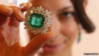 A model holding an emerald and diamond broach