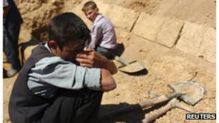 A boy reacts near the grave of his father in a cemetery in Duma neighbourhood of Damascus