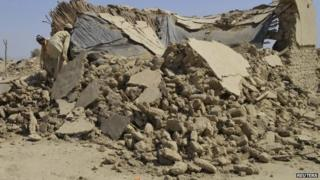 Survivors of an earthquake collect their belongings near the rubble of a mud house after it collapsed following the quake in the town of Awaran, south-western Pakistani province of Baluchistan, September 25, 2013