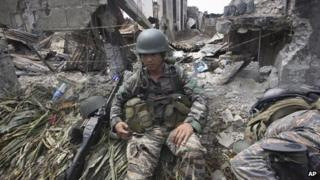 A government trooper rests amidst the ruins at the site of a three-week standoff in Zamboanga city, southern Philippines.