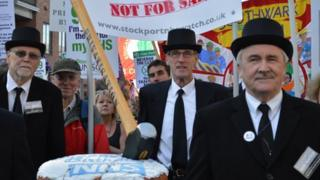 """Protesters carrying a """"Happy Birthday NHS"""" cake with a privatisation sledge hammer crushing it."""