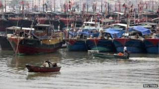 Fishermen drive a boat next to fishing ships docked at a port to shelter from Typhoon Wutip in Sanya, Hainan province, 29 September 2013