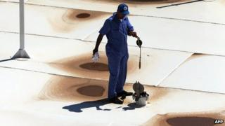 A Libyan oil worker from the Libyan National oil and gas company walks at the the Zawiya oil installation (22 Aug 2013)