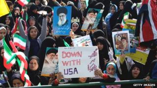 Iranian demonstrators hold anti-US slogans and portraits of supreme leader, Ayatollah Ali Khamenei during a rally in Tehran's Azadi Square in February 2013