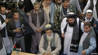 """Afghan Mujahideen leader Abdul Rassoul Sayyaf (C, seated) waits to register as a candidate for the presidential election at Afghanistan""""s Independent Election Commission (IEC) in Kabul October 3, 2013."""