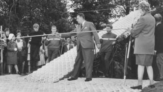 Fred Pontin cuts the ribbon to open the slope with members of the British Ski Team, Swiss Ski Instructors and Torquay's enthusiastic skiers watching.