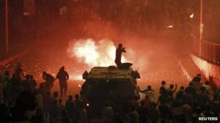 A riot police officer fires rubber bullets at members of the Muslim Brotherhood during clashes in Cairo October 6