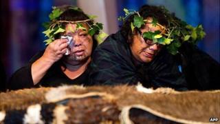 Two members of the Tainui Waka Alliance tribe weep beside the 20 Maori mummified tattooed heads (Toi Moko) returned to New Zealand during a ceremony at Te Papa Museum in Wellington