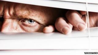 Man looking through blind