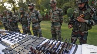 Indian army soldiers stand behind a display of seized arms and ammunition at a garrison in Srinagar, October 7, 2013.