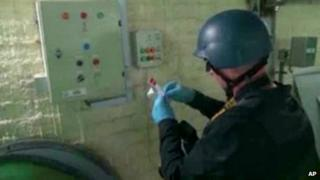 This image made from video broadcast on Syrian State Television on 8 October purports to show a chemical weapons expert taking samples at a chemical weapons plant at an unknown location in Syria