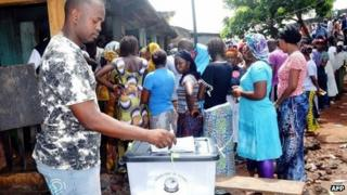 A Guinean voter casts his ballot as others queue at a polling station in Conakry on 28 September 2013