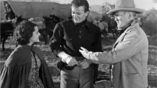 John Wayne standing between two people in The Oregon Trail
