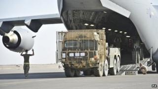Military truck being loaded onto a C-17 aircraft for return to the UK