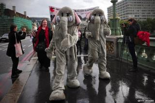 Two protesters in elephant costume march across Westminster Bridge