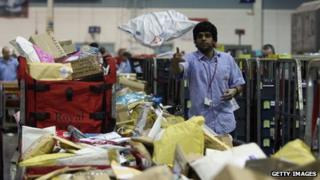 A person throwing a parcel in a Royal Mail sorting office