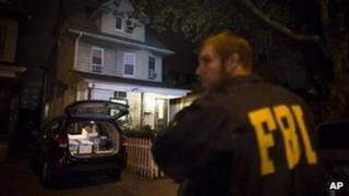 An FBI agent stands guard as evidence sits in the trunk of a vehicle at the Brooklyn residence of Rabbi Mendel Epstein during an investigation, 10 October 2013