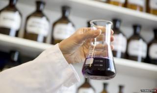 Scientist holding beaker