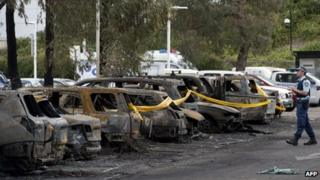 A police officer walks next to burnt vehicles following a fire at Sydney's Olympic Park on 14 October 2013
