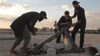Opposition fighters prepare to fire a mortar shell during clashes with government forces in the northern rebel-held Syrian city of Raqqa (6 October 2013)