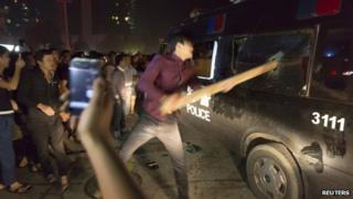 A man breaks the window of a police van with a wooden plank during a protest in Yuyao