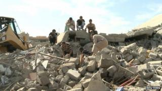 Civilians gather at the site of a bomb attack in the village of Mwafaqiya, in Nineveh province