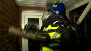 Police officer outside house being raided