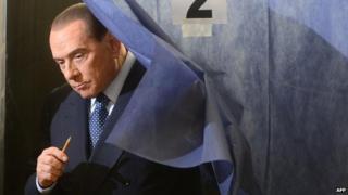 Silvio Berlusconi leaving a voting booth, Milan (file photo 24 Feb)