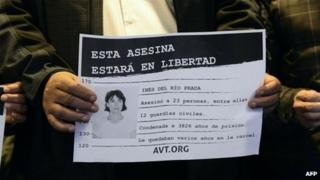 "An activist holds a placard which reads ""This murderer will be free"", alongside a picture of Ines Del Rio"