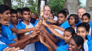 Children from the nine provinces of Sri Lanka hold the baton with John Rankin, British High Commissioner