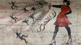 """A mural showing a woman spraying a number of men with the slogan: """"No to harassment"""" in Cairo (May 2013)"""