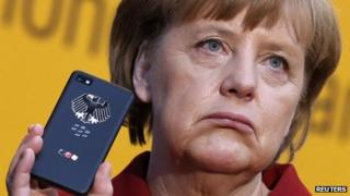 The German Chancellor, Angela Merkel holds a Smartphone